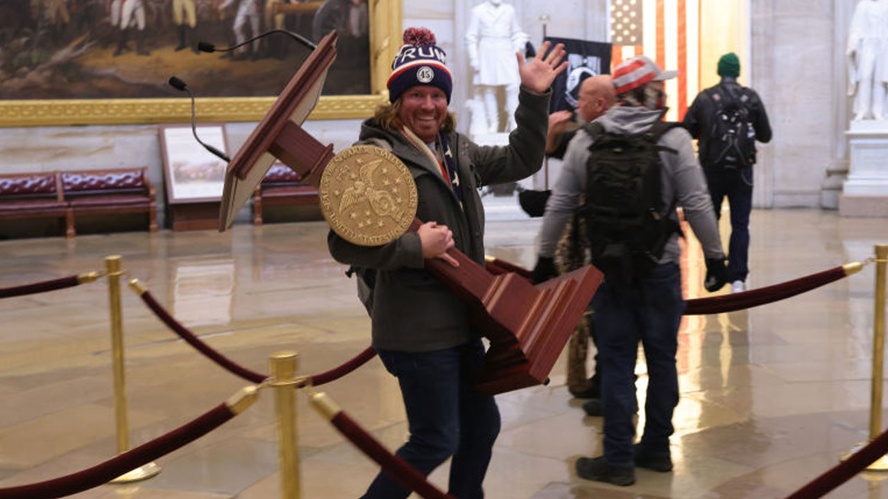 Smiling man carrying lectern during Capitol riots identified |  RochesterFirst